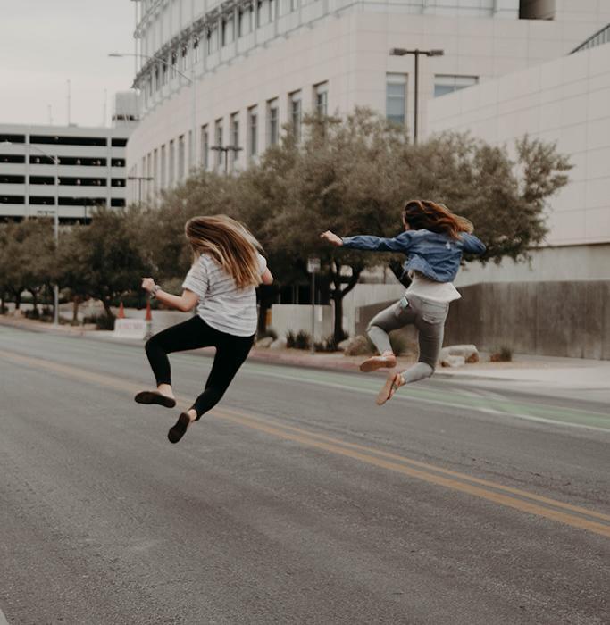 deux jeunes femmes en joie qui sautent dans la rue pour exprimer une libération après un atelier d'expression corporelle animé par Véronique Ruotte