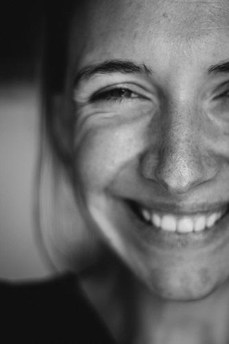 jeune femme épanouie et riant illustrant les bienfaits des ateiers utilisant le  Rire et la Dansel