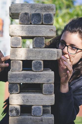 jeune femme construisant un pile de pierre style Kapla pour illustrer la construction de l'individu par éclat de toi